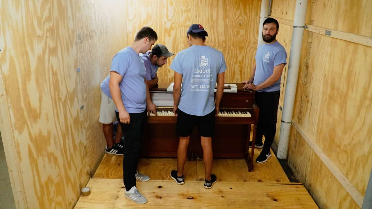 Movers packing piano